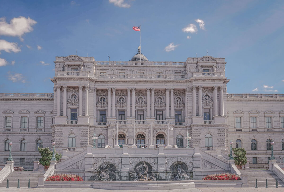 Library of Congress full facade showing summer in Washington D.C. The sky is a pale blue. And the building is huge with three fountains in the front.