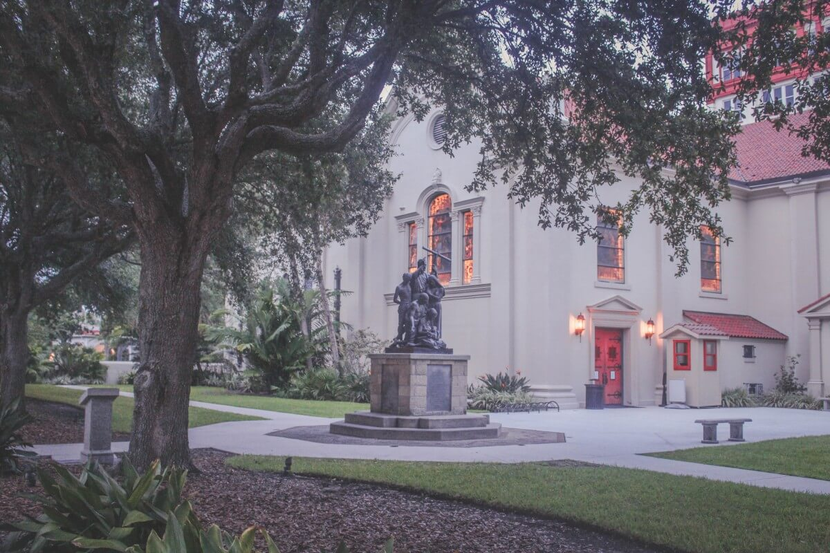 Cathedral Basilica Of St. Augustine at sunset with soft lights and a statue out back