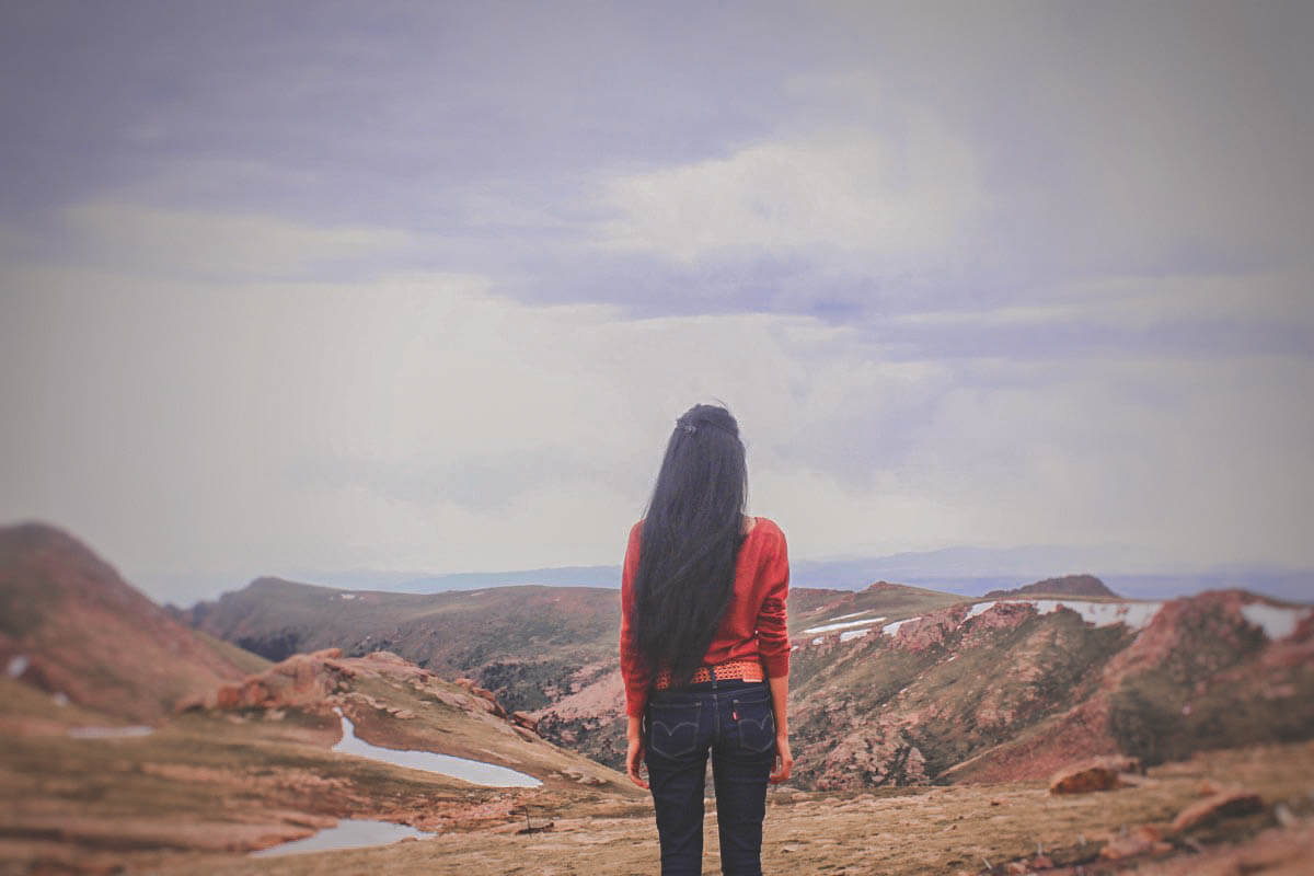 Girl standing on top of mountain with little pools of water in front of her