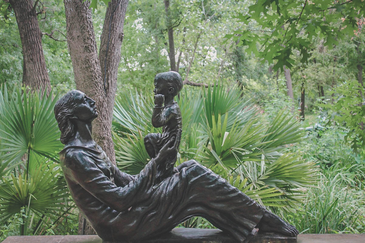 A mother looking at her son statue in Umlauf Sculpture Garden