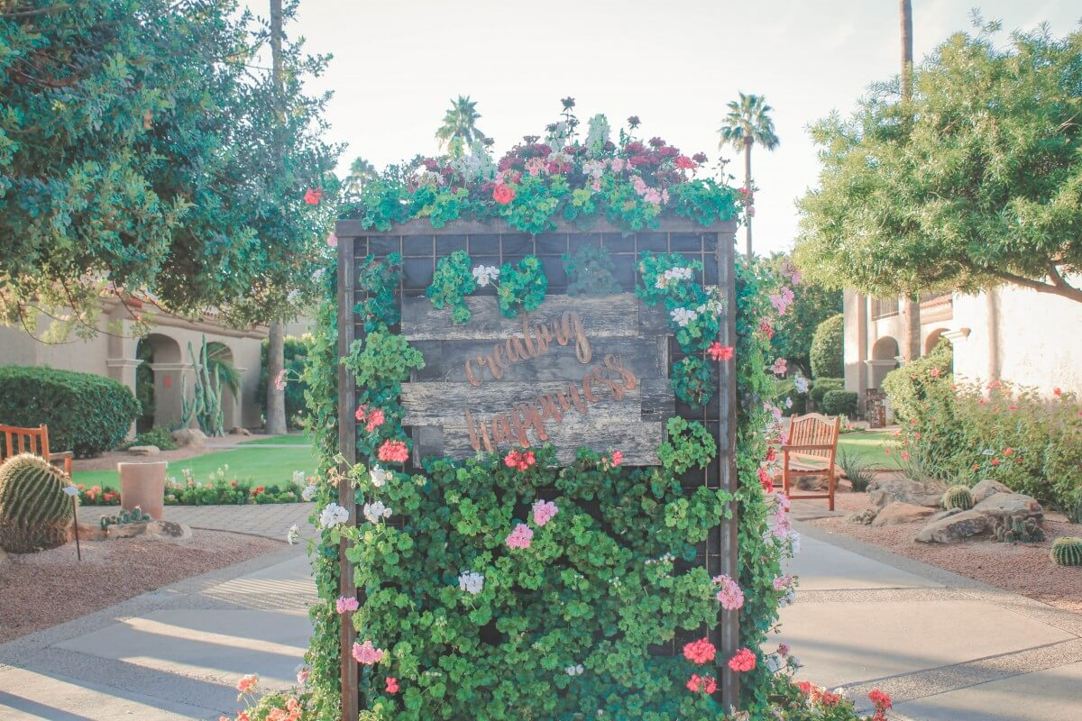 The Plaza Resort in Scottsdale garden pathway with a creating happiness sign.