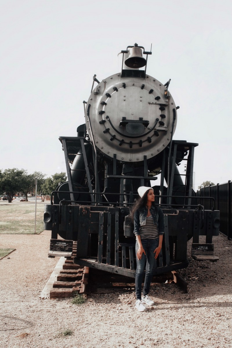 gawky awkward teenager in front of a train at the Frisco Heritage Museum
