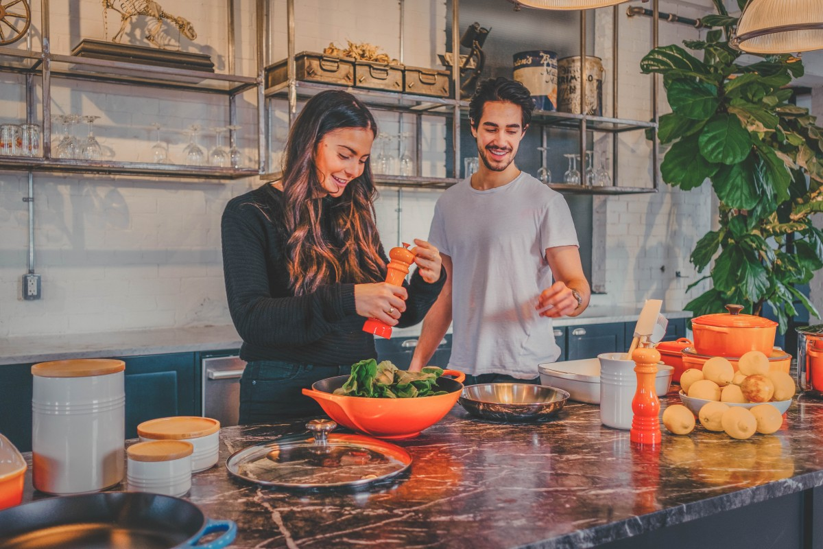 couple making a salad during their at home cooking class
