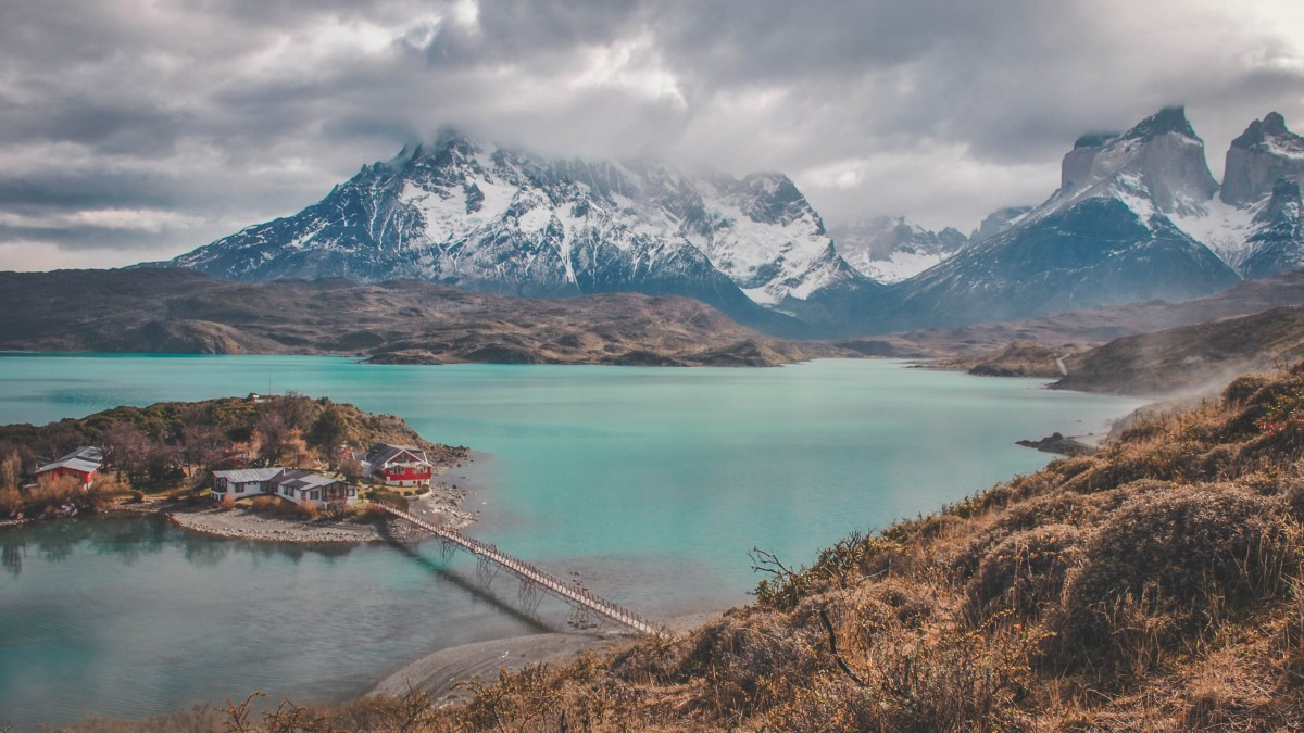 aqua blue waters of Patagonia with a view of Paine Massif covered by fog