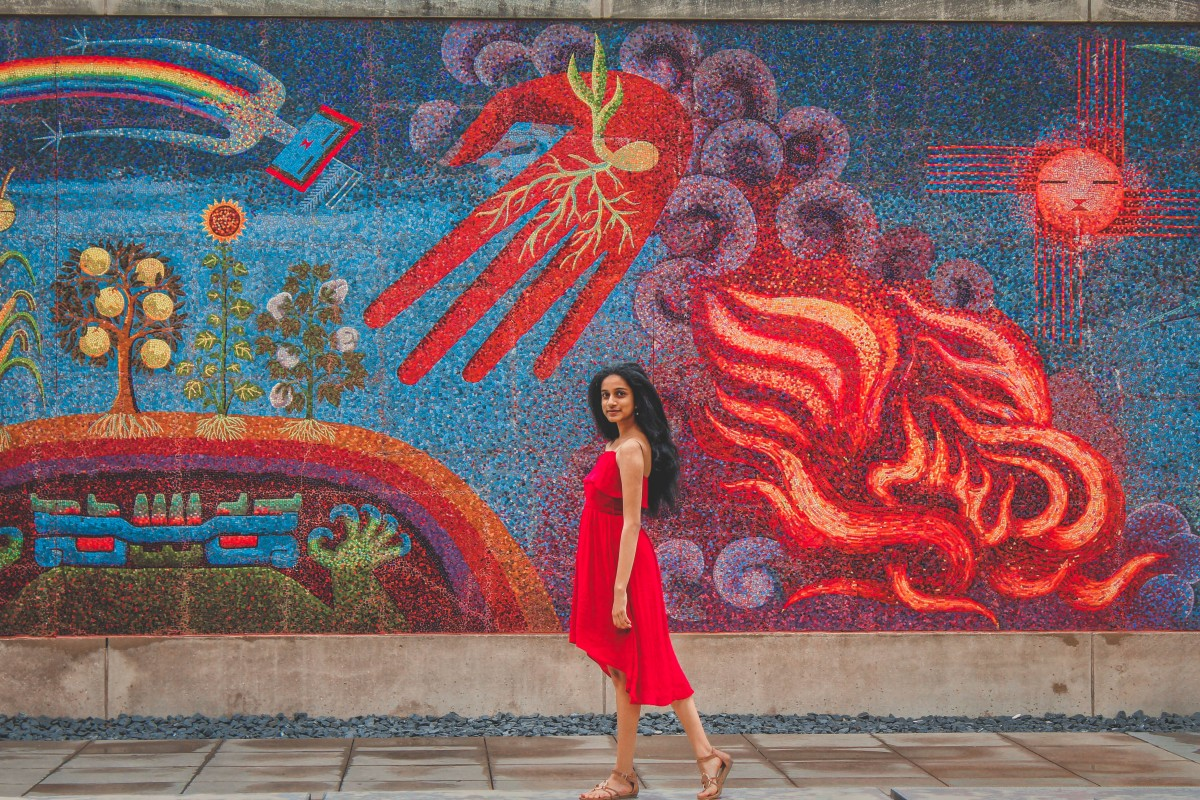 girl in red dress standing in front of a bright colorful mural outside of the DMA, located in the Dallas Arts District