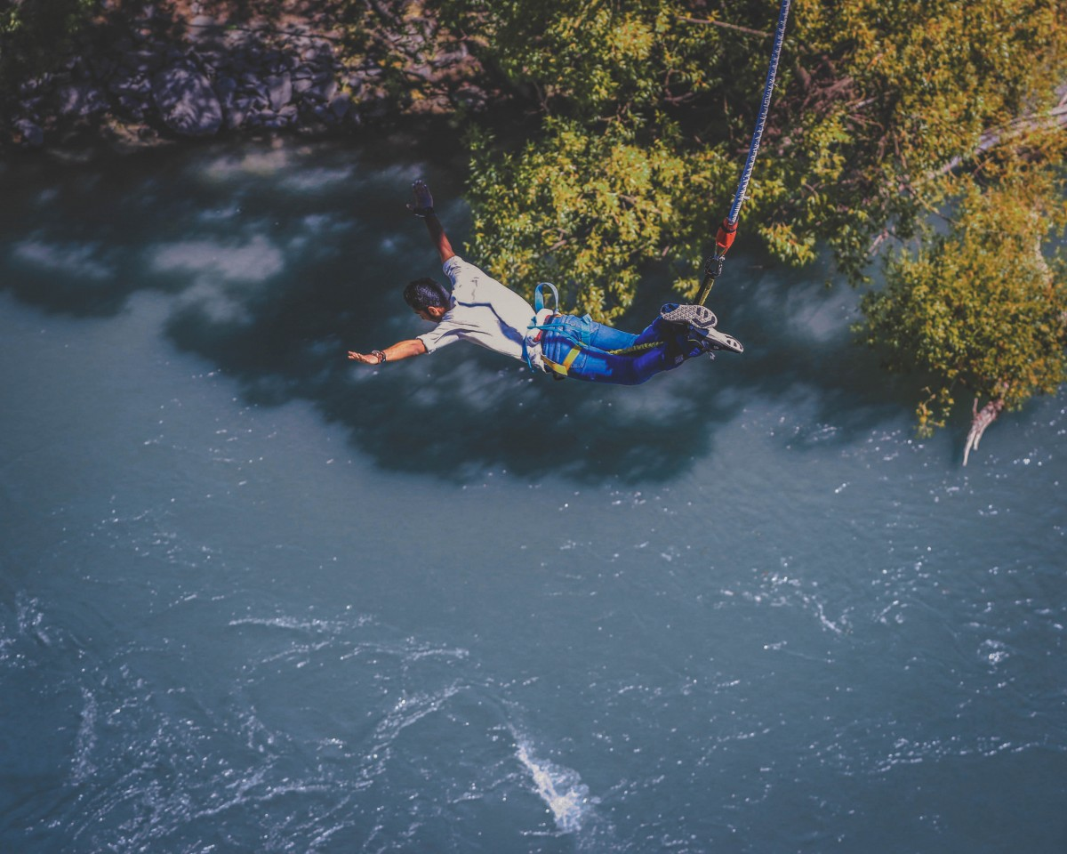 photo of man bunjee jumping as featured photo for adventurous road trip questions for couples