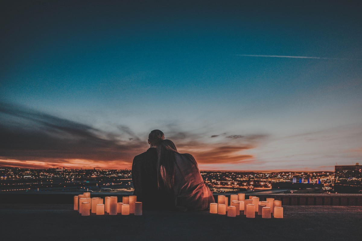 couple at sunrise with small lamps surrounding them - road trip questions for couples