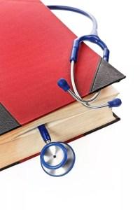 Ein blaues Stethoskop liegtn in einem medizinischen Buch