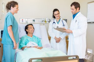 Young doctors discussing notes while nurse and patient looking at them in hospital room