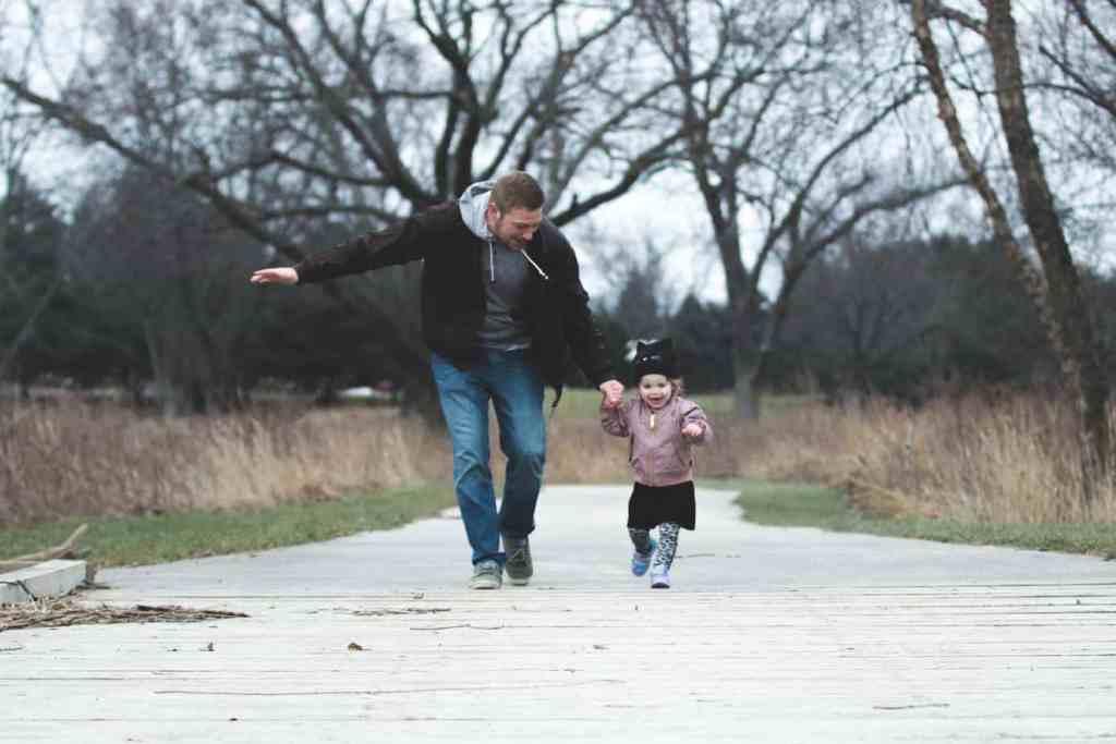 Vater läuft mit Tochter an der Hand