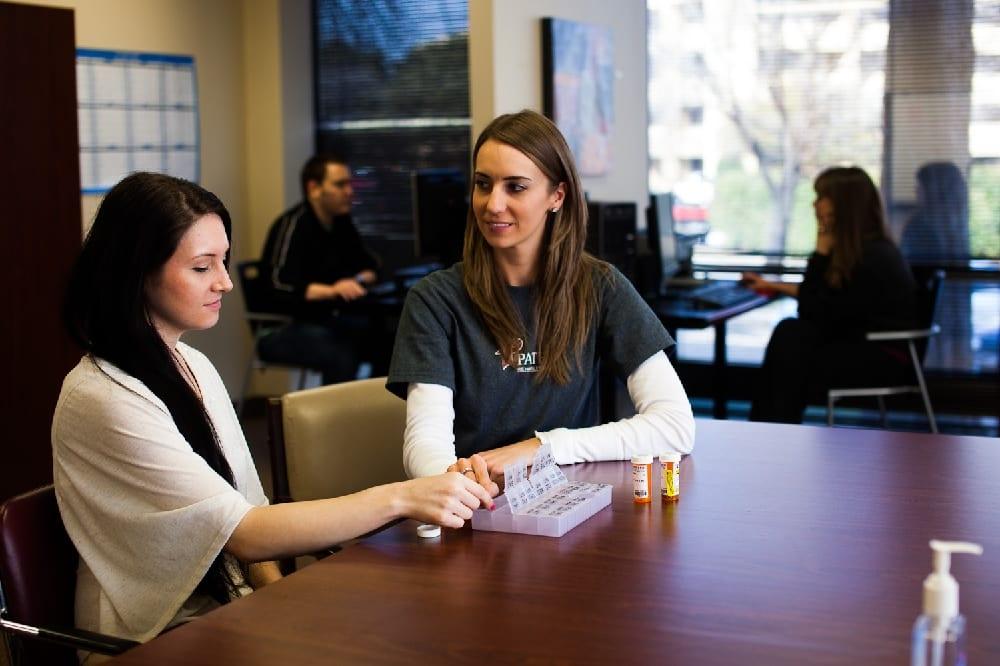 Women at table sorting medication