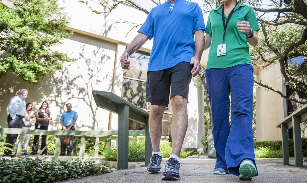 stroke brain injury patient walking with a therapist