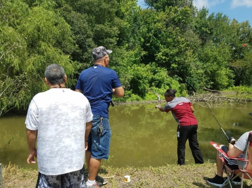 supported living activities program residents fishing at pond