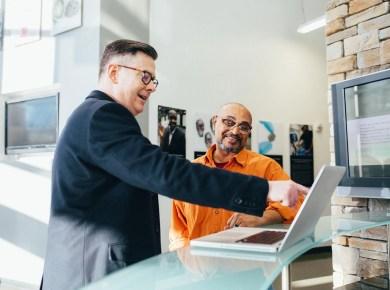 ein Berater gibt einem Kunden Imagefilm am Laptop Marketing Tipps