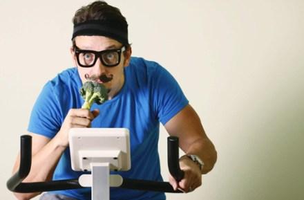 Egy nagy bajuszos féfi vastagkeretes szemüvegben szobabiciklizik és kezében brokkoli.