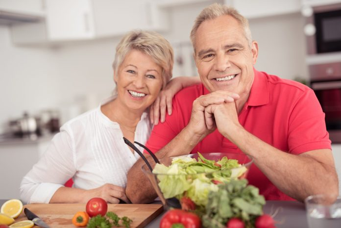 Portrait of a Happy Senior Couple Sitting at the Kitchen Table with a Bowl of Fresh Salad, Smiling at the Camera.