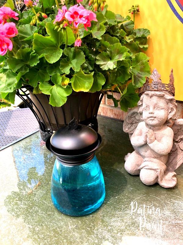 statue, geraniums, tiki lamp