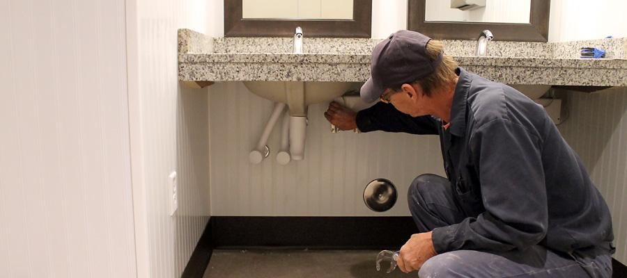 Greg working on bathroom sink pipes