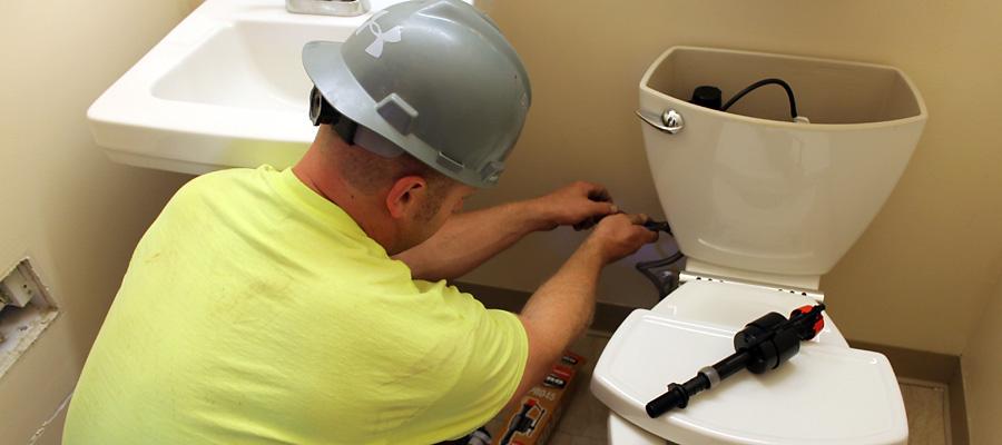 plumber working on bathroom toilet