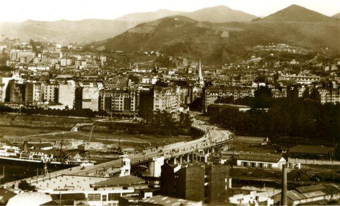 Otra imagen histórica del puente de Deusto. En primer término, a la izquierda, la chimenea de los Talleres de Deusto. (Postal, Colección Joaquín Cárcamo)