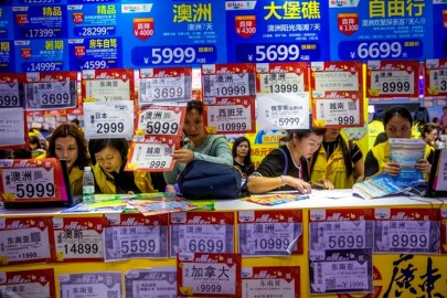 In this March 3, 2018, photo, people check on travel packages offered by travel agencies during the Guangzhou International Travel Fair in Guangzhou, China. (Chinatopix via AP)