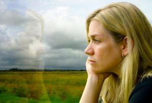 Woman looks out window loney