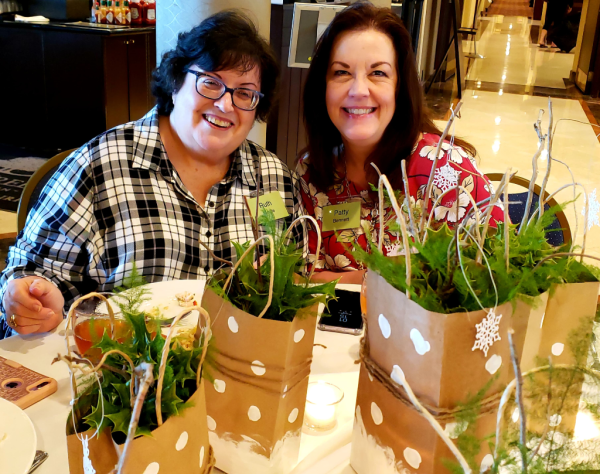 Ruth Bingle's Craft your Christmas stamping and paper crafting Retreat, Oct. 2018. Table centerpieces with painted brown bags, greenery and die cut snowflakes.