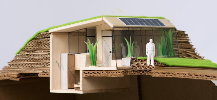 Een maquette van de Tiny House prijsvraag Enschede, bestaande uit karton, balsahout. De maquette is opengesneden aan de zijkant zodat je ook goed de badkamer en de slaapplaats kan zien. Architect Enschede