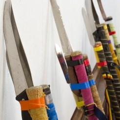 Cornered, 110x350x30cm, hockey sticks, kitchen knives, electrical tape, belts (2016)