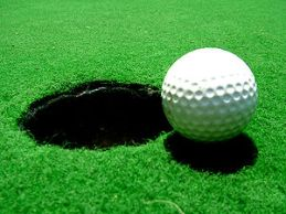 A golf ball directly before the hole
