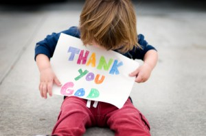 child holding thank you god sign