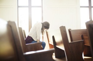woman alone in church pew