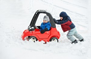 Little boy pushing toy car stuck in snow