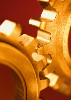 interlocking gold gears on a red background