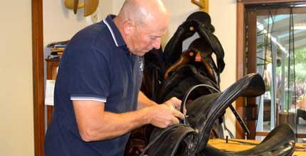 Image of Paul Buckland repairing a saddle