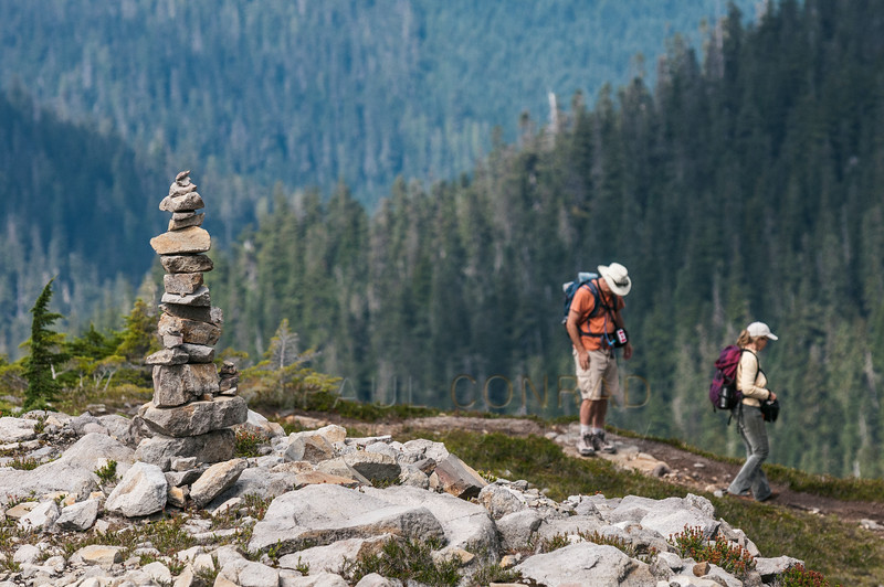 © Paul Conrad/Pablo Conrad Photography - A couple  pause at a cairn along the Chain Lakes Trail several hundred yards past the Ptarmigan Ridge turn-off. I came around the corner and saw them then the cairn. I used a shallow depth of field to set them against the forest.