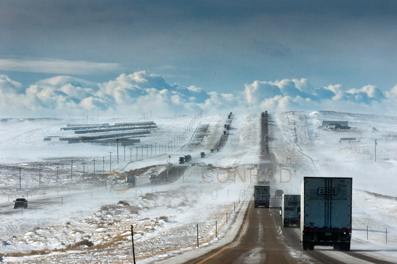 © Paul Conrad/ Pablo Conrad Photography - High winds blow snow across the highway as storm clouds form on the horizon in the west along Interstate 80 in southwest Wyoming.