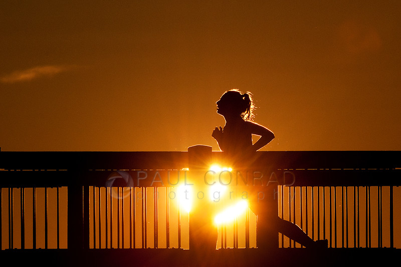 © Paul Conrad/Pablo Conrad Photography - A runner jogs along the Boardwalk at Boulevard Park in Bellingham, Wash., during a blazing Sunset on Sunday evening April 14, 2013.