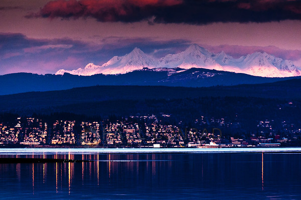 © Paul Conrad/Pablo Conrad PhotographyThe setting Sun glints off windows and street signs in Bellingham, Wash., as it bathes the snow capped peaks of The Twin Sisters of the Cascade Mountain range in its last rays.