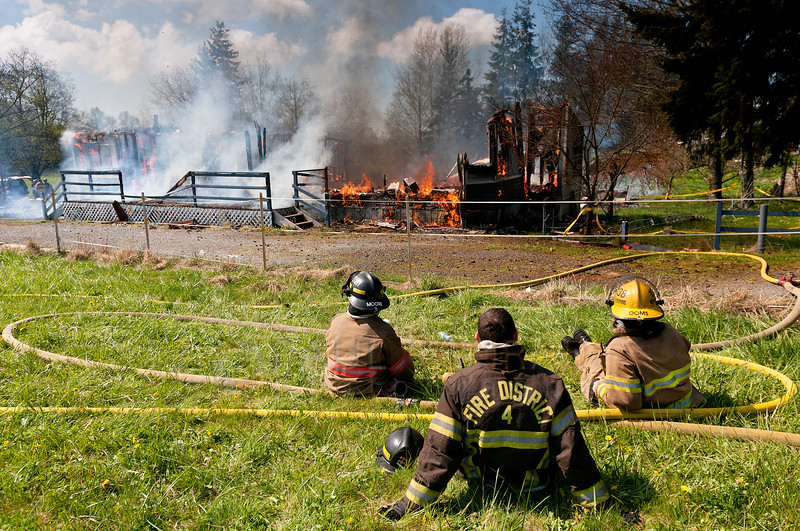 © Paul Conrad/ Pablo Conrad Photography - Several Whatcom County firefighters take a rest as they monitor a controlled training fire on Kline Street one mile east of Meridian Avenue north of Bellingham on Saturday afternoon April 12, 2014.
