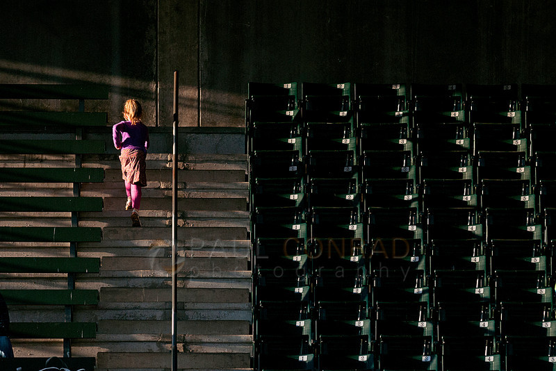 © Paul Conrad/ Pablo Conrad Photography - A little girl runs up the stairs in the east stands during the NWC Track & Field Championship at Civic Field and Stadium in Bellingham, Wash., during the early evening April 25, 2014.