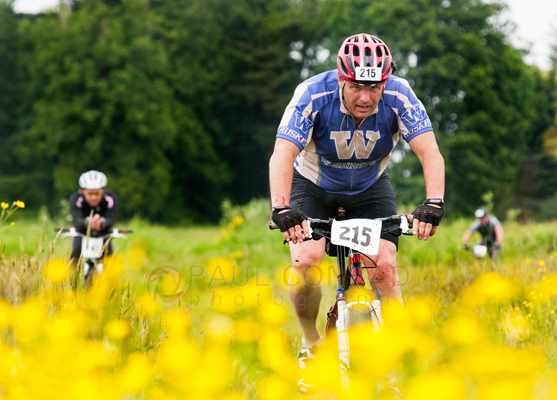 © Paul Conrad/The Bellingham - Dan Garrison of Team Mandelbaums traverses on open field along Labounty Road in the mountain biking leg of the 2014 Ski to Sea Race on Sunday, May 25, 2014 in Ferndale, Wash.