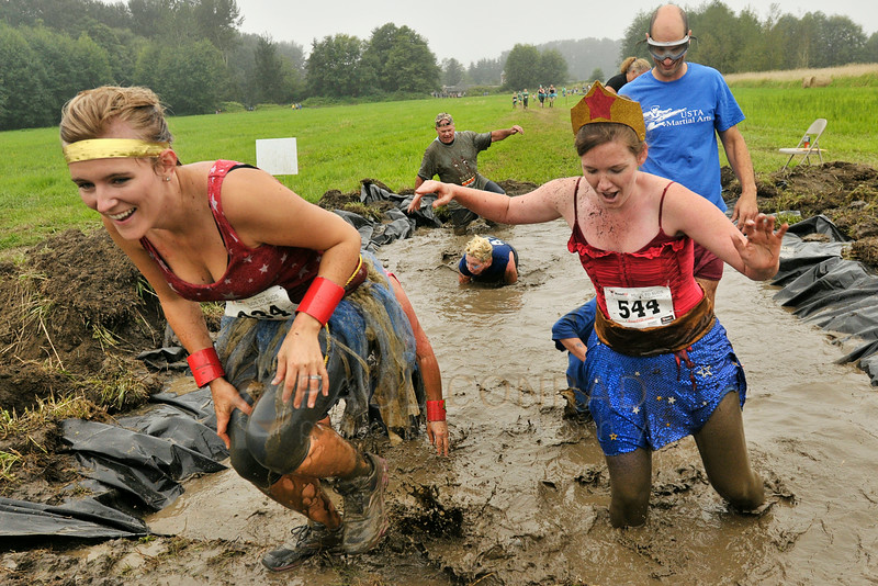 © Paul Conrad/The Bellingham Herald - Racers climb out of the Holee Kow mud pit during the 3rd annual Mud to Suds race on Saturday morning August 16, 2014, at Hovander Park in Ferndale, Wash. Nearly 2000 people ran the 2.5 mile course negotiating 22 obstacles including mud-filled pits, hay bales, and a soap foam tunnel. The event raised funds for the Girls Scouts of Western Washington.