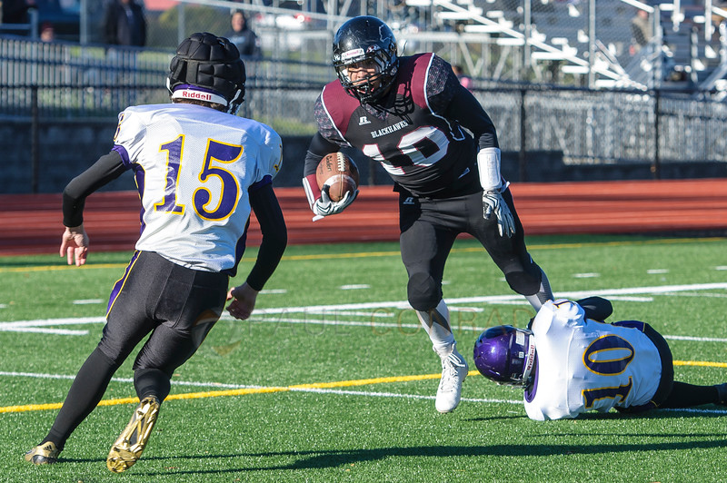 Quilcene's Eli Harrison (15) moves in on Lummi's Dashawn Lawrence (10) as a Quilcene's A.J. Prator (10) graps his feet during the second quarter in the 1B state quarterfinals on Saturday afternoon Nov. 21, 2015, at Lummi Nation School in Lummi, Wash. Lummi went on to defeat Quilcene 40 to 0 to advance to the semi-final. (© Paul Conrad/The Bellingham Herald)