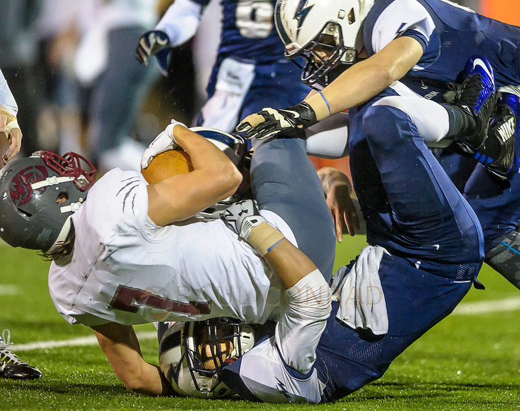 Squalicum's Creighton Kaui (16), bottom, and Kyle Basart (63) take down WF West's Nathan Anglin (7) at the line of scrimmage during the first quarter on Saturday evening Nov. 14, 2015, in the first round of District 2A State Playoffs at Civic Field in Bellingham, Wash. Squalicum defeated WF West 31 to 29.