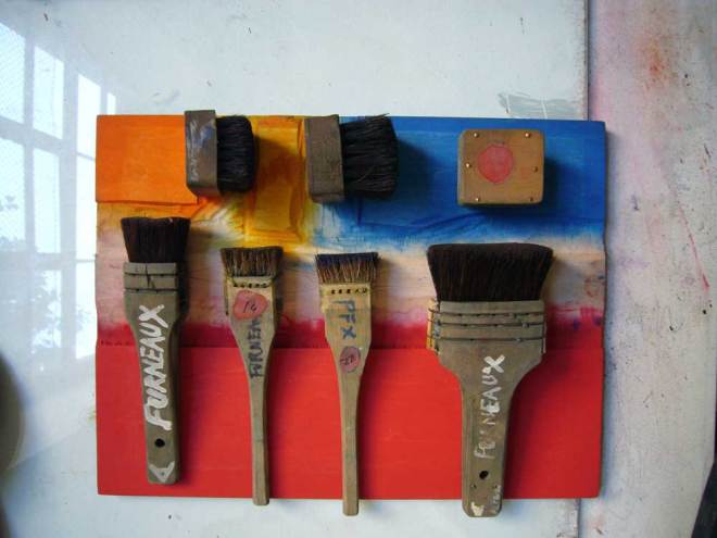 Brushes on an inked piece of woodblock