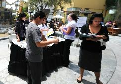 Job seekers wait in line to have their resumes reviewed at the Anaheim/Orange County Job Fair in Anaheim, Calif., on June 2.