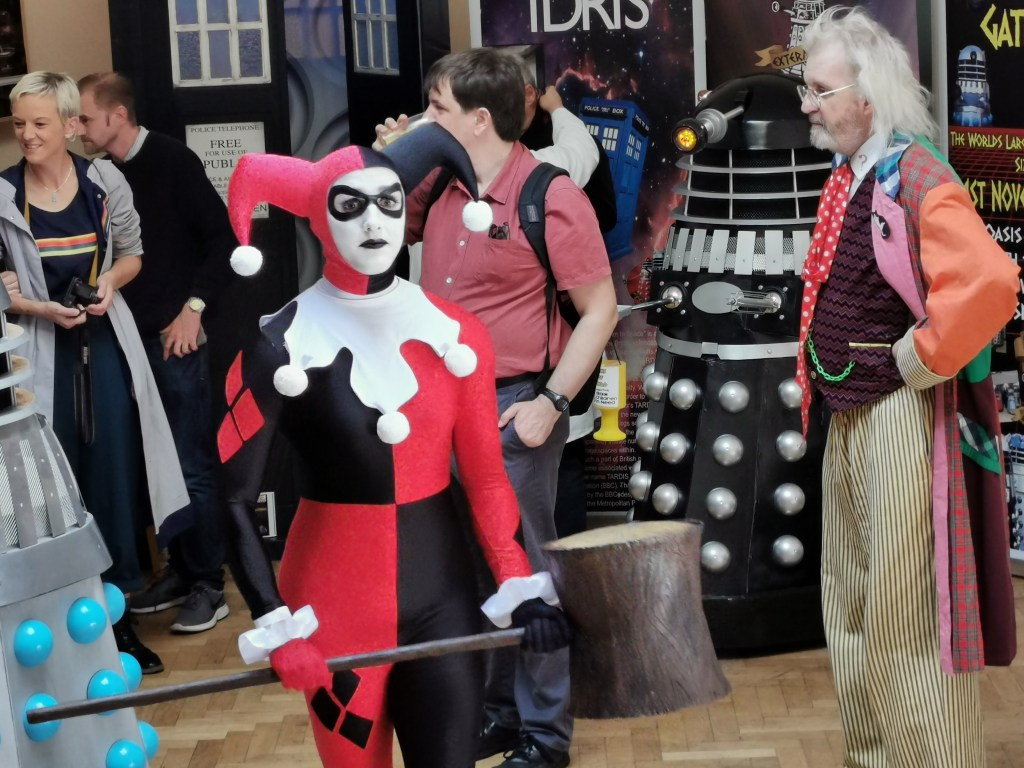 An image of Harley Quinn and the Sixth Doctor Who cosplayers.
