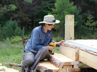 Kade working on rustic steps for the ladies' yurt.