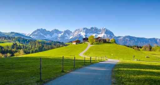 Idyllic alpine scenery, farmhouse in front of snowy mountains, Kitzbühel, Tyrol, Austria